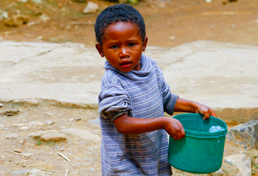 Boy holding fresh water from air in bucket